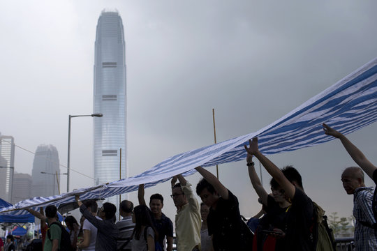 Protesters standing under a plastic sheet tip rain water from the top of the tent as they camp outside Hong Kong's Chief Executive Leung's office in Hong Kong