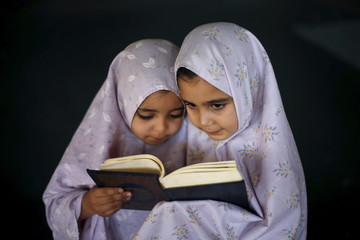 Palestinian girls read the Koran as they attend a Koran memorisation lesson during summer vacation inside a mosque in Gaza City