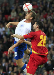 England's Kevin Davies is challenged by Montenegro's Miodrag Dzudovic during their Euro 2012 qualifying soccer match at Wembley Stadium in London