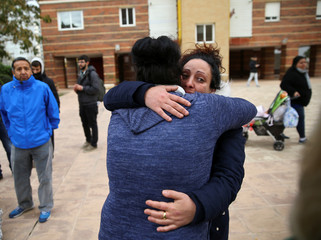Guabala de la Cruz is comforted by a neighbour after Spanish riot policemen evicted the family from their home in Parla, outside Madrid, Spain