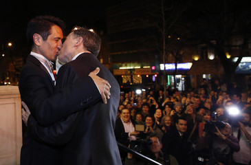 British couple David Cabreza and Peter McGraith kiss amidst a cheering crowd after their wedding at Islington Town Hall in London