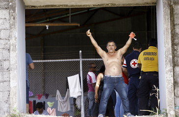 A Cuban migrant raises his arms after receiving food at a temporary shelter in the town of La Cruz near the border between Costa Rica and Nicaragua