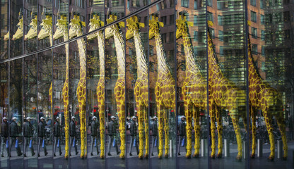 A giraffe made of Lego bricks is reflected in a glass front of a house in Berlin