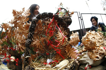 Women buy dried oak leaf branches and wheat, symbols of the traditional Yule log, in Belgrade