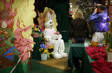 A person dressed as the Easter Bunny holds a baby while getting a picture taken at the Broadway Market in Buffalo