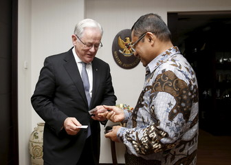 Australia's new Trade Minister Andrew Robb exchanges name cards with Indonesia's Industry Minister Saleh Husin before their meeting in Jakarta