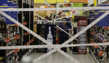 Workers puts tape to close an aisle with hard liquor in a supermarket in Prague