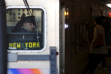 A conductor looks out the rear window of a New Jersey Transit commuter train bound for New York City at the Secaucus Junction station in Secaucus