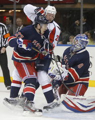 New York Rangers Lundqvist gloves the puck behind teammate McDonagh and Washington Capitals Chimera during the NHL game in New York