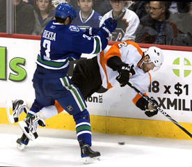 Canucks' Bieksa knocks Flyers' Leino off his feet during their NHL hockey game in Vancouver