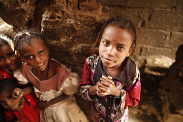 Girls from the Akhdam community pause as they are photographed in a slum area in Sanaa