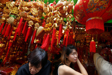 Costumers are seen inside a decorations shop ahead of the upcoming Year of the Rooster celebrations in Chinatown, Bangkok