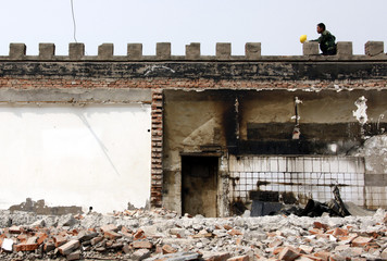 A man holds his helmet while on the roof of a partially demolished dwelling in a hutong in Beijing