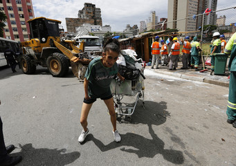 A woman pulls a shopping cart filled with her belongings as workers from a cleaning company remove a shack, in a part of Sao Paulo's Luz neighborhood known to locals as Cracolandia