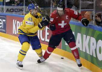 Sweden's Moller fights for the puck with Switzerland's Streit during their Ice Hockey World Championship game in Prague