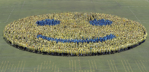 Students stand in formation on a field as a smiley face which they attempt to break a world record to celebration their 110th university anniversary in Nanjing