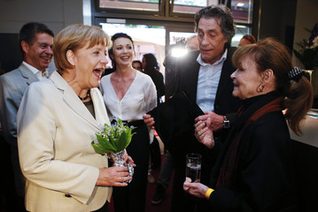 "German Chancellor Merkel and her husband laugh as they talk to German actors before the screening of ""The Legend of Paul and Paula"" at a cinema in Berlin"