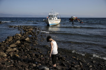 A migrant boy stands next to the sea as refugees and migrants arrive on a boat, seen in the background, on the Greek island of Lesbos