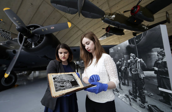 Research assistants Samantha Jolley and Lucy Dale inspect the scrapbook belonging to war correspondent Virginia Irwin at The American Air Museum