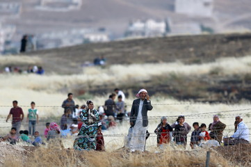 Syrian Kurds from Kobani wait behind the border fences to cross into Turkey as they are pictured from the Turkish border town of Suruc in Sanliurfa province, Turkey