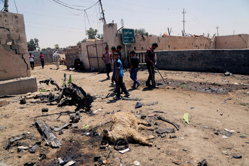 People gather at the site of a suicide bomb attack in a southeastern suburb of Baghdad