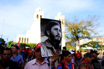 A man holds a picture of Fidel Castro as part of a tribute in San Salvador