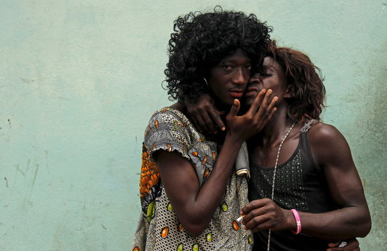 Men dressed as women kiss as they take part in a parade during the Popo (Mask) Carnival of Bonoua, east of Abidjan