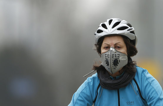A cyclist wears a mask with an air filter as she cycles through Hyde Park in London