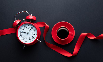 cup of coffee, alarm clock and ribbon