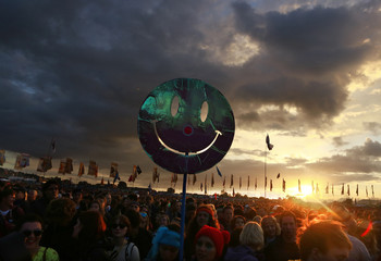 A smiley face is held up by a festival-goer as the sun sets in front of the Other Stage at Worthy Farm in Somerset, during the Glastonbury Festival