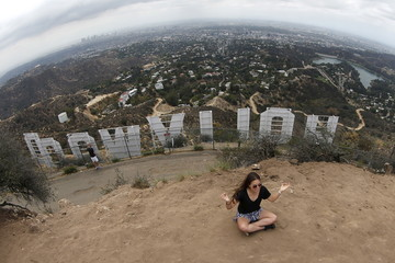 A woman strikes a yoga pose for a friend's photo behind the Hollywood sign in Los Angeles