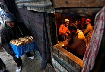Bakers work inside their shop on a cold winter morning in Srinagar