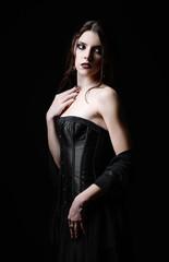 Dramatic portrait of beautiful sad goth woman among the dark