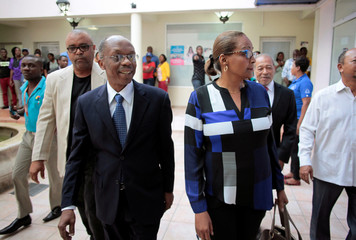 Presidential candidate Maryse Narcisse, of Fanmi Lavalas party, and former President Jean-Bertrand Aristide arrive at the Electoral Provisional Council in Petion Vile