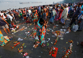 "A Hindu woman worships after taking a holy dip in the Ganga river on the occasion of the annual Hindu festival of ""Karthik Purnima"" or full moon night, in Kolkata"