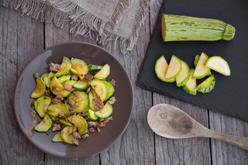 Zucchini cooked with meat in brown plate on wood