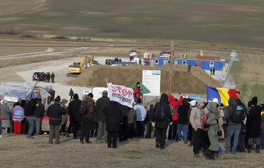 Villagers and environmental activists gather in front of a site of U.S. oil major Chevron, during a protest against exploration for shale gas in Pungesti