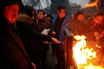 People burn incense sticks and pray for good fortune at Yonghegong Lama Temple on the first day of the Lunar New Year of the Rooster in Beijing