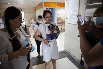 Zhang Yibi holds a picture of her son Lei Chi, a firefighter who is among those missing after the huge explosion at the port in Tianjin, China, as she visits a hospital looking for him