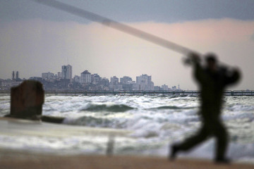 Part of the Gaza Strip is seen in the background as an Israeli man fishes at Zikim beach, near Ashkelon