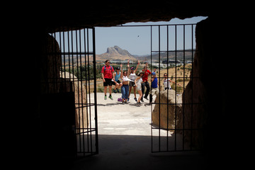 People jump as they take a photo with the Pena de los Enamorados mountain outside the Menga dolmen at Antequera Dolmens Site in Antequera