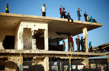 Palestinians stand atop a damaged building as they wait for their relatives to return to Gaza from Egypt through Rafah border crossing, in the southern Gaza Strip