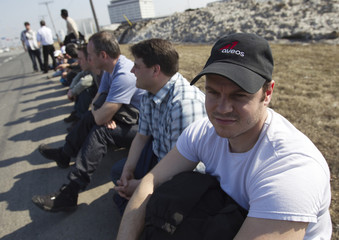 Employees of Aveos Fleet Performance Inc. sit by side of road near their head office in Montreal