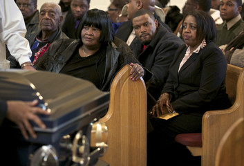 Shirley Chambers and other family members look on as the casket of her son Ronnie Chambers, a victim of gun violence, is rolled out of the church following his funeral in Chicago