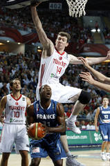 France's Pietrus looks to the basket as Turkey's Asik leaps and Tunceri looks on during FIBA Basketball World Championship game in Istanbul