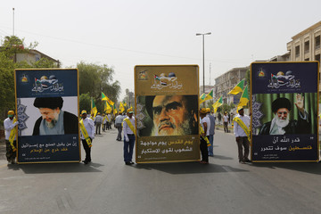 Iraqi Shiite Muslim men from Shi'ite Badr organisation hold portraits of leaders during a parade marking the annual al-Quds Day in Baghdad