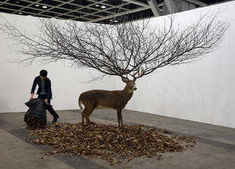 A worker places leaves around an installation by South Korean artist MyeongBeom Kim at Art Basel's 2015 edition in Hong Kong