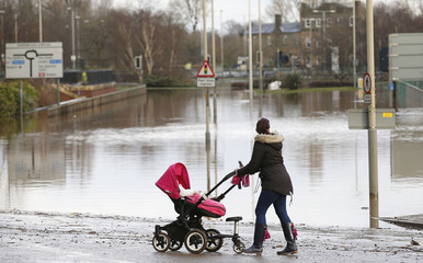 A woman stops to look at the city centre submerged under flood waters in Carlisle, north west England