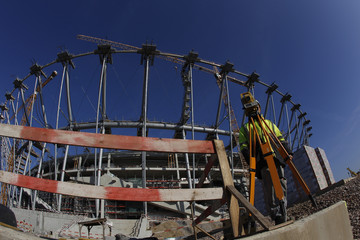 A worker takes measures at the construction site of the National Stadium in Warsaw
