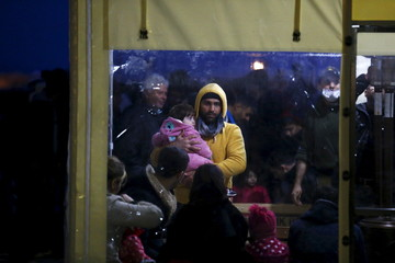 Syrian refugees wait for the finishing of their registration formalities after they were brought to a coast guard station at the Turkish coastal town of Kucukkuyu following a failed attempt of crossing to the Greek island of Lesbos